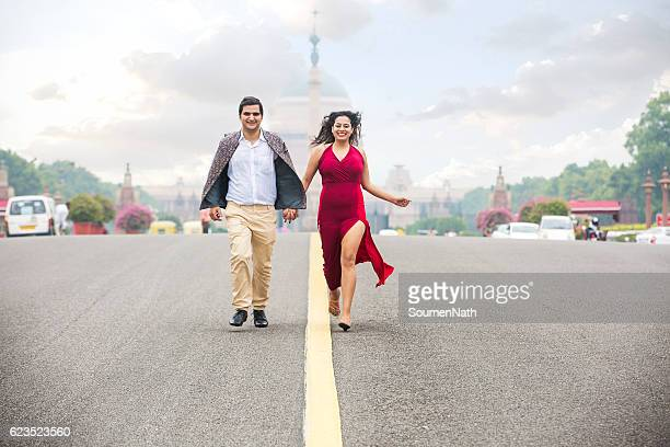 happy young couple, running on the road holding their hands - women photos stock photos and pictures