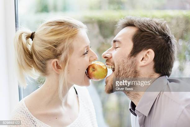 Happy young couple sharing an apple