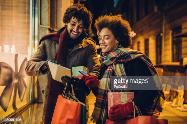 Happy young couple shopping for Christmas presents online