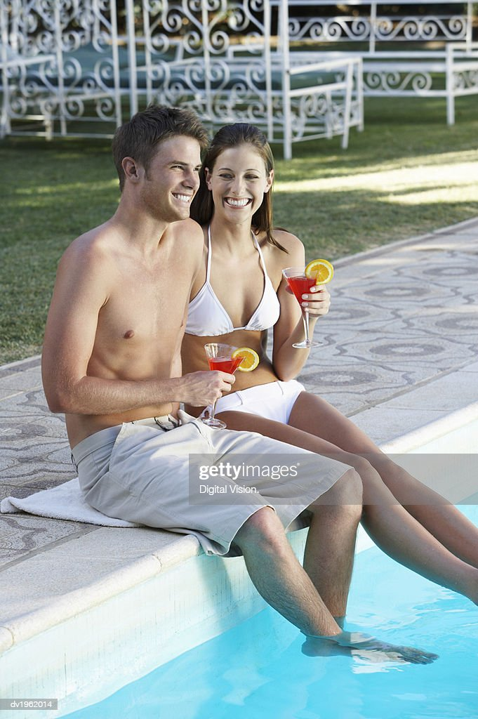 Happy Young Couple Sit by a Swimming Pool Holding Cocktail Glasses : Stock Photo