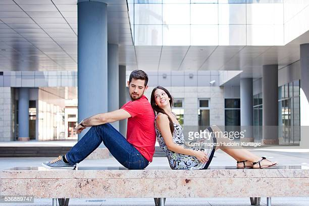 Happy young couple sits back to back on campus