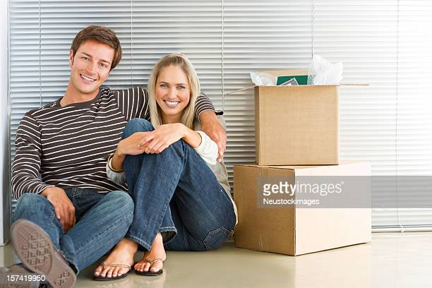 Happy young couple sitting by boxes