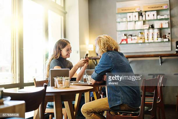 Happy young couple sitting in a coffee shop
