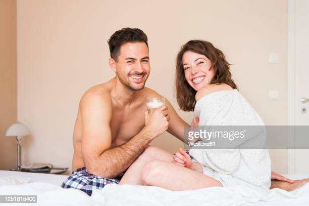 happy young couple sitting on bed at home - dalgona stock pictures, royalty-free photos & images