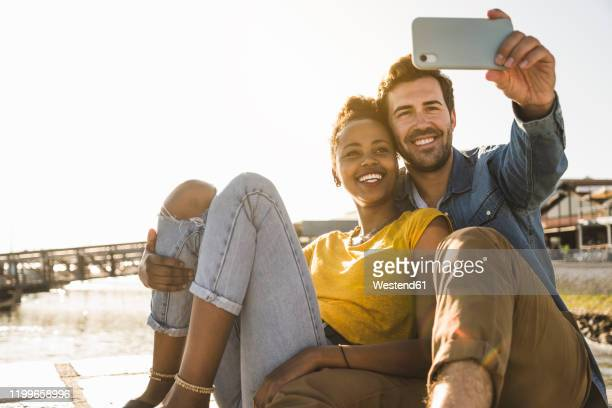 happy young couple sitting on pier at the waterfront taking a selfie, lisbon, portugal - uferviertel stock-fotos und bilder