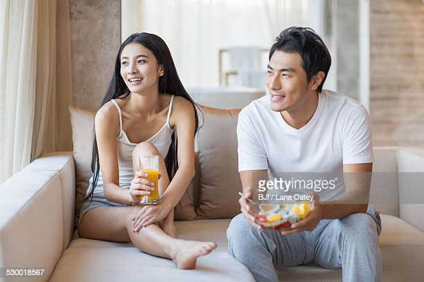 Happy young couple sitting on the sofa