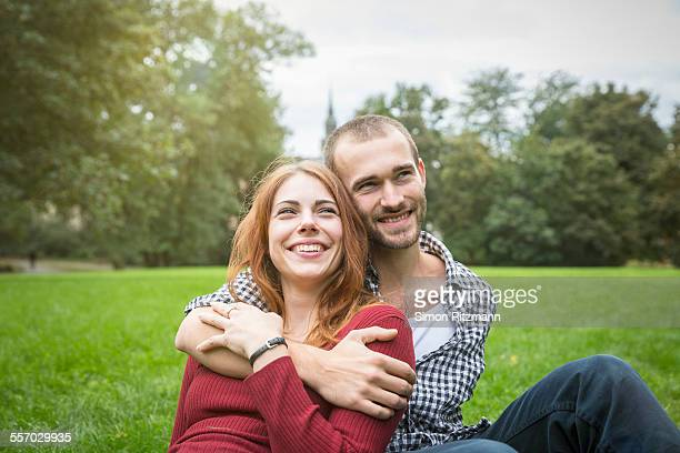 Happy young couple sitting outdoors in grass