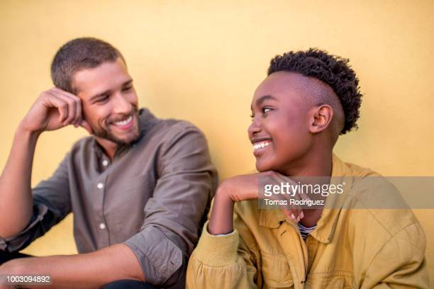 Happy young couple smiling at each other in front of yellow wall