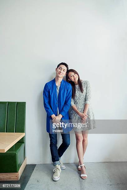Happy young couple standing by wall