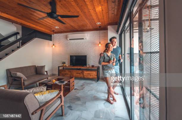 Happy young couple standing by window at home