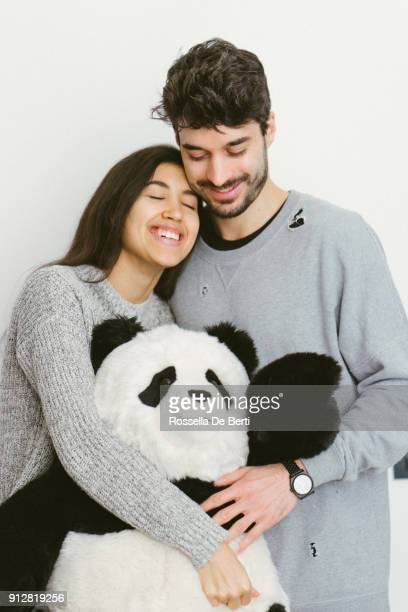 Happy young couple standing embracing a soft toy