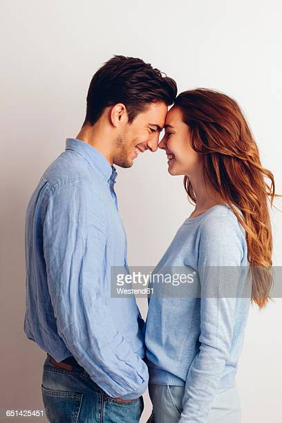 happy young couple standing face to face in front of white background - face to face stock pictures, royalty-free photos & images