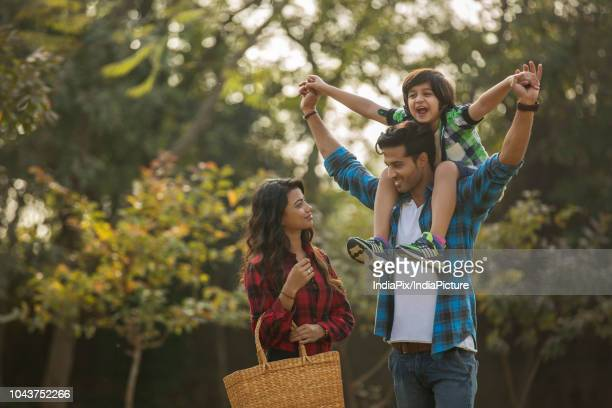 happy young couple standing in a garden with the man carrying their son on his shoulders and the woman carrying a basket. - indian subcontinent ethnicity stock pictures, royalty-free photos & images