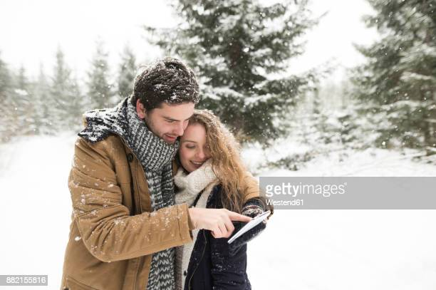 Happy young couple standing in snow-covered winter forest using cell phone