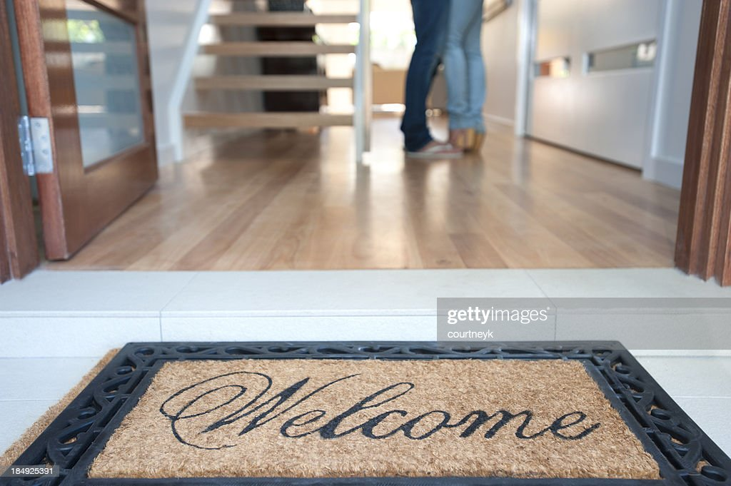 Happy young couple standing inside their new house : Stock Photo