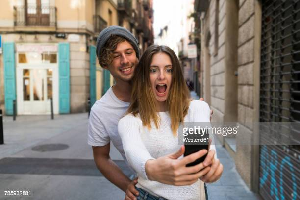 Happy young couple taking a selfie the city