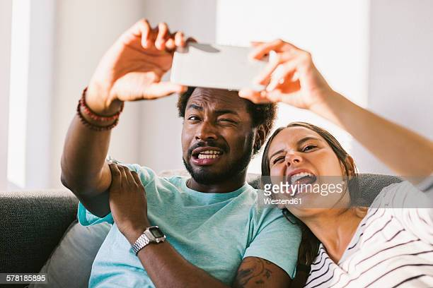 Happy young couple taking fotographs of themselves with smart phone