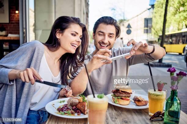 happy young couple taking photo of food at outdoors restaurant - terrasse de café photos et images de collection