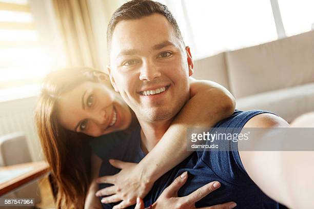 Happy young couple taking sefies at home