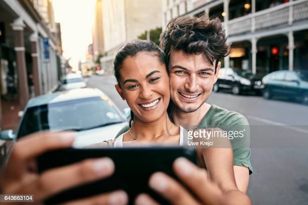 Happy young couple taking self portrait in the city