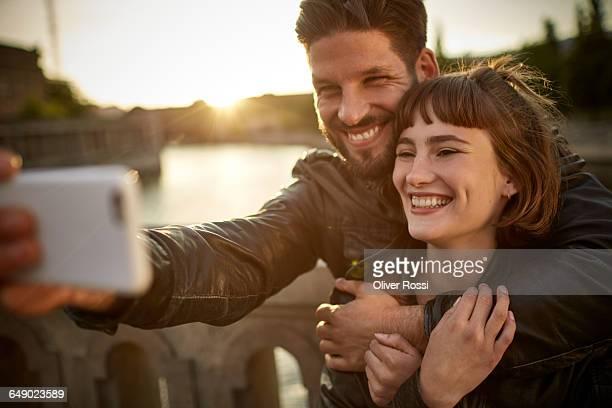 happy young couple taking selfie by the riverside - kurzes haar stock-fotos und bilder