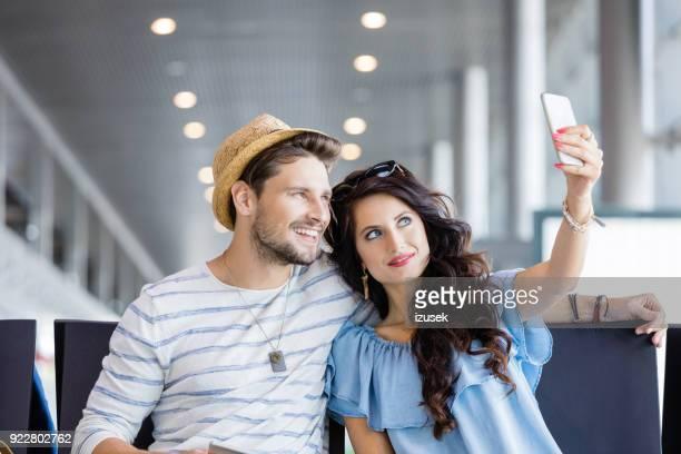 felice giovane coppia che si fa selfie nella lounge dell'aeroporto - izusek foto e immagini stock