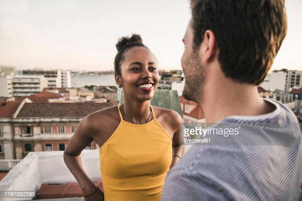 happy young couple talking on rooftop in the evening - flirting stock pictures, royalty-free photos & images