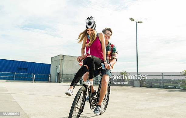 happy young couple together on a bicycle - girls stock-fotos und bilder