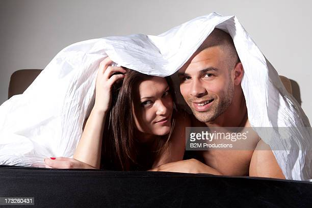 Happy Young Couple Under Bedsheet