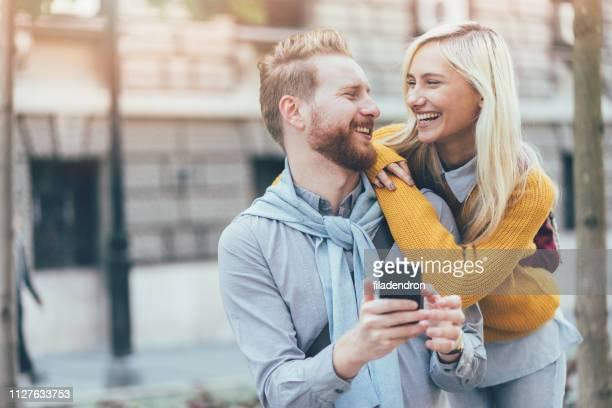 heureux jeune couple à l'aide d'un smartphone - bonne nouvelle photos et images de collection