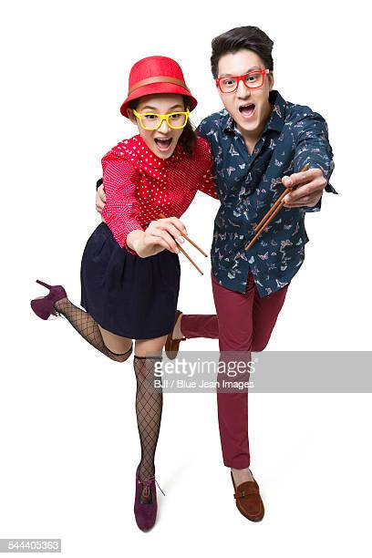 Happy young couple using chopsticks