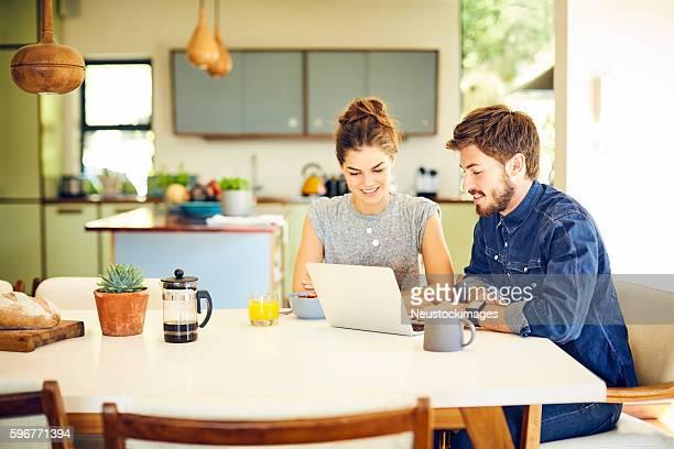 giovane coppia felice usando il laptop sul tavolo per la prima colazione - coppia eterosessuale foto e immagini stock