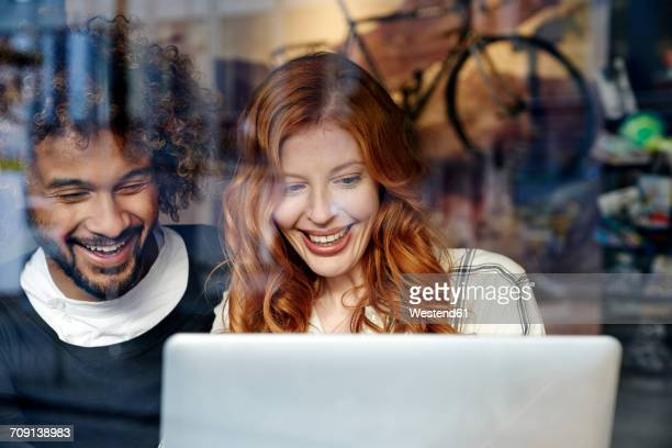 Happy young couple using laptop behind windowpane
