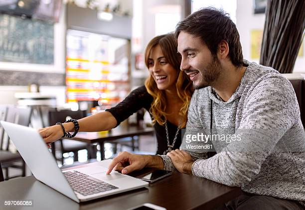 Happy young couple using laptop in a pub
