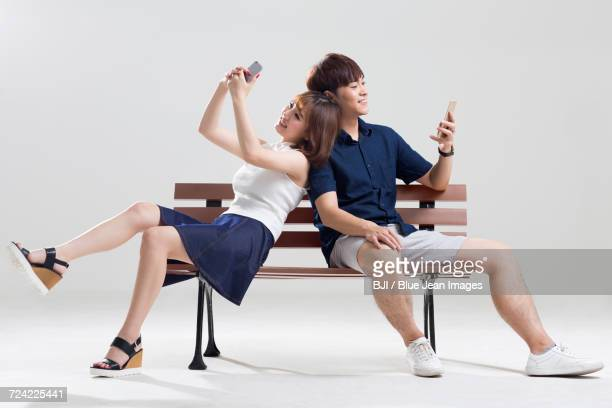Happy young couple using smart phones