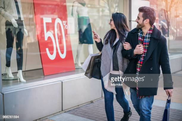 happy young couple walking on the street and staring at the shop window - saldi foto e immagini stock