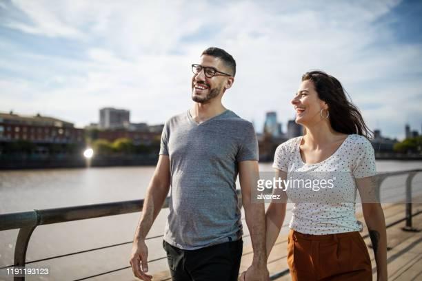 glückliches junges paar zu fuß zusammen auf stadtpromenade - uferpromenade stock-fotos und bilder