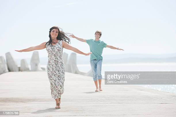 Happy young couple with arms outstretched on pier