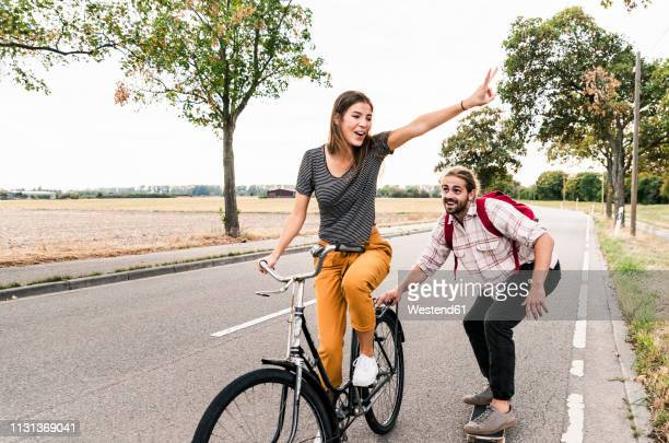 happy young couple with bicycle and skateboard on country road - sorglos stock-fotos und bilder