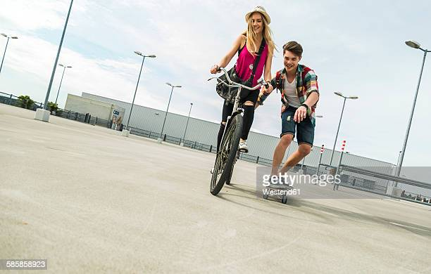 Happy young couple with bicycle and skateboard