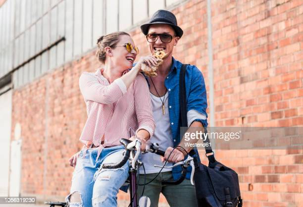 happy young couple with bicycle sharing a snack - teilen stock-fotos und bilder