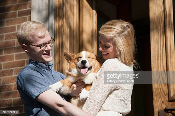 happy young couple with corgi dog in arms outside front door - americas next top dog stock pictures, royalty-free photos & images