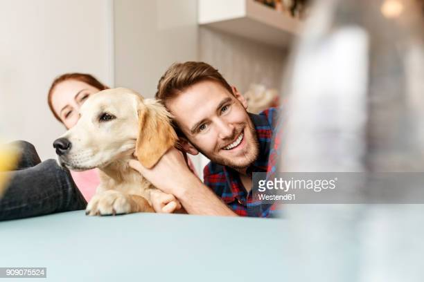 Happy young couple with dog at home