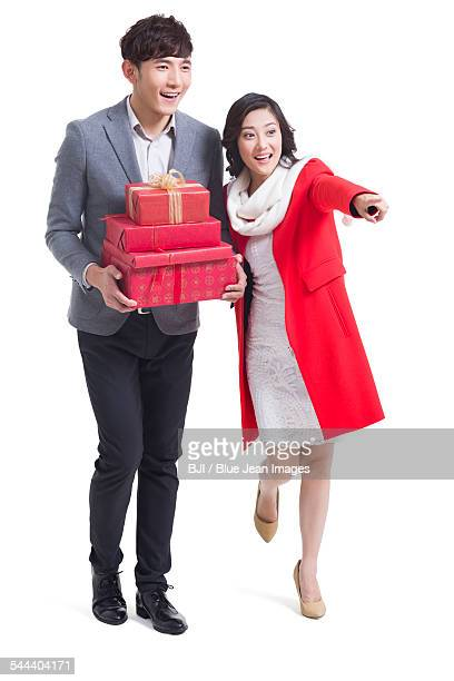 Happy young couple with gifts looking at view
