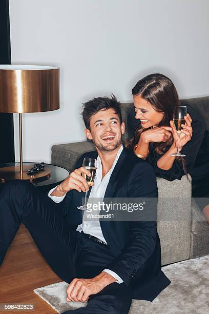 happy young couple with glasses of champagne at sofa - elegância imagens e fotografias de stock
