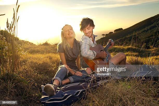 Happy young couple with guitar on blanket in meadow
