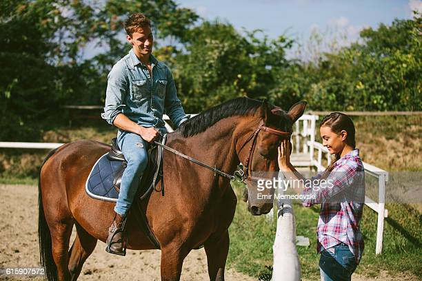 Happy young couple with horse outdoors.
