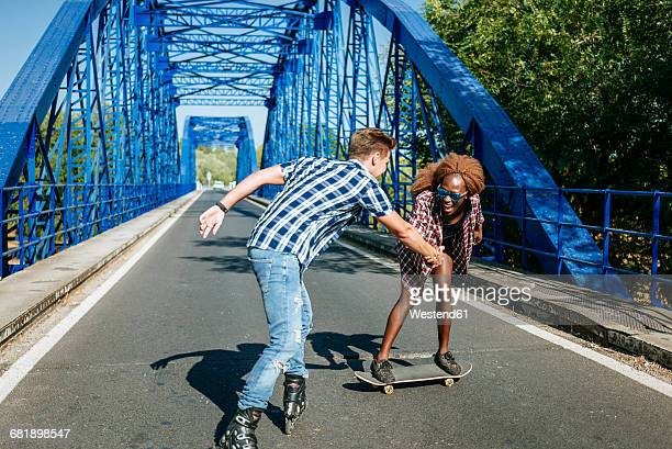 happy young couple with inline skates and skateboard on a bridge - inline skating stock pictures, royalty-free photos & images