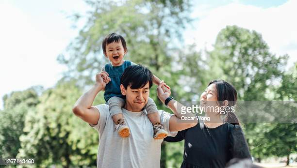 happy young couple with little girl on her father's shoulders at park on a sunny day - asian and indian ethnicities stock pictures, royalty-free photos & images