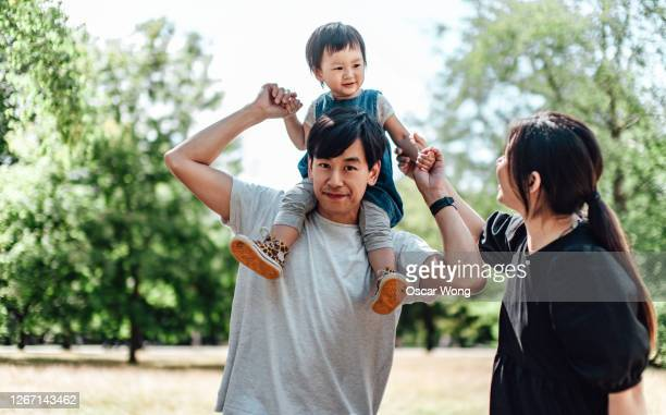 happy young couple with little girl on her father's shoulders at park on a sunny day - couple stock pictures, royalty-free photos & images